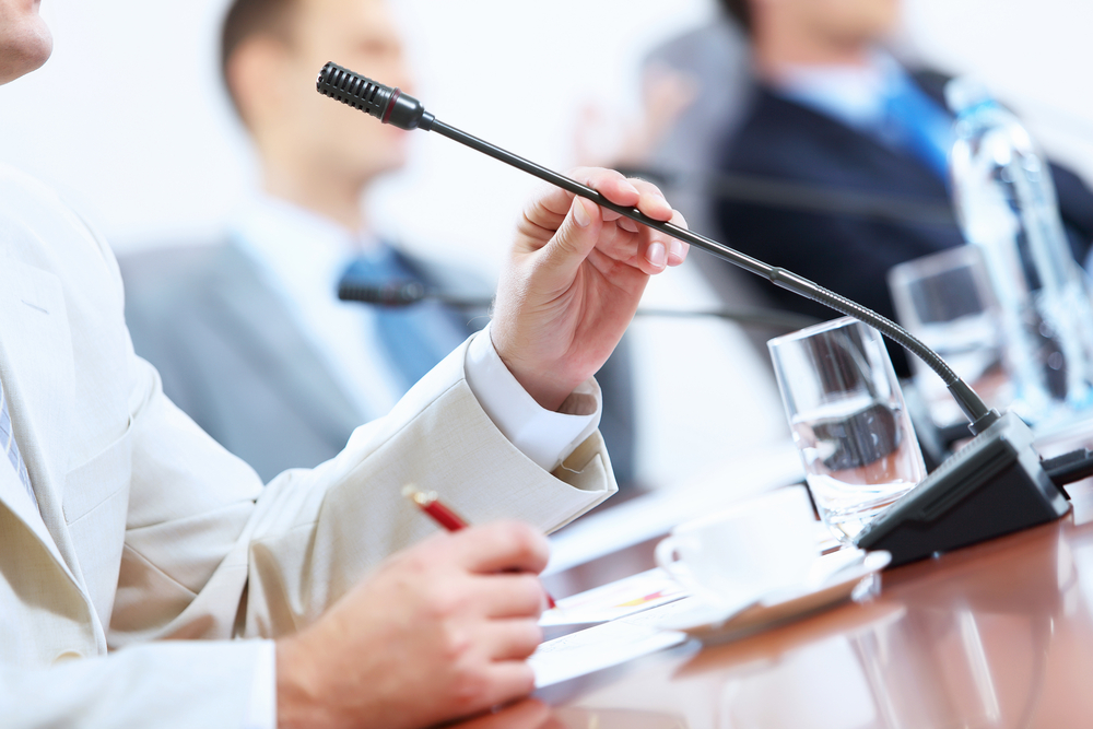 Image of businessmans hands holding microphone at conference
