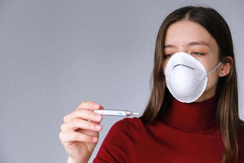 woman-in-face-mask-checking-thermometer-3987152